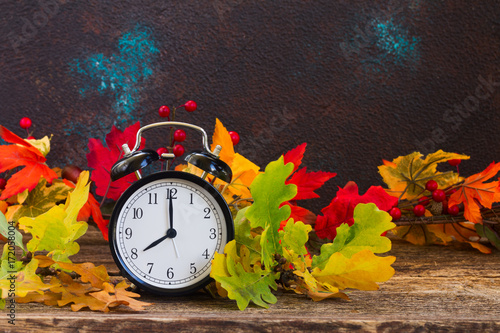Autumn time - fall multicolored leaves with alarm clock