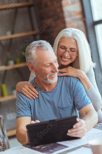 Fototapeta Loving aged couple using tablet at home obraz