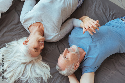 Fotografia  Top view of a cheerful loving couple lying in bed together