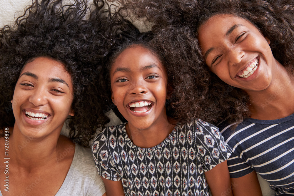 Fototapety, obrazy: Overhead Portrait Of Three Teenage Sisters Lying On Bed At Home