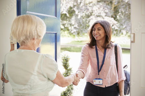 Photo  Senior woman greeting female care worker making home visit