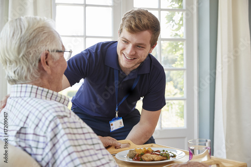 Photo Male care worker serving dinner to a senior man at his home