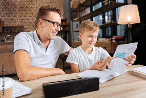 Fototapety, obrazy: Pleasant boy describing charts to his father