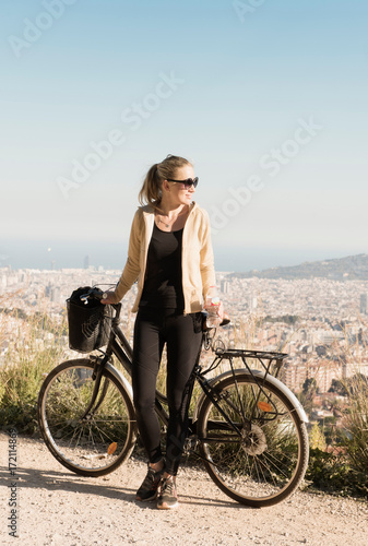In de dag Barcelona Woman sightseeing on bicycle, city in background, Barcelona, Catalonia, Spain