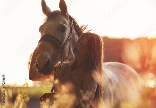 Woman hugging her horse at sunset, autumn scene