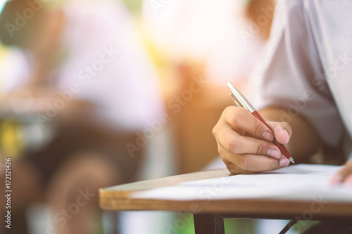 Fotografia  Closeup to hand of student  holding pen and taking exam in classroom with stress for education test