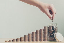 Hand Of Male Or Female Putting Coins In Jar With Money Stack Step Growing Growth Saving Money, Concept Finance Business Investment, Copy Space For Your Text