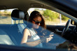 Attractive woman texting in a car on the road