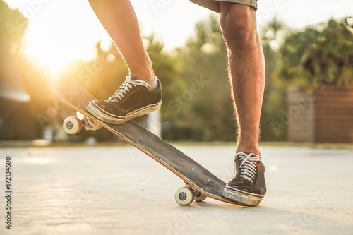 Closeup of man legs with skateboard at sunset outdoors