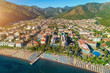Aerial view of beautiful city, sandy beach with chaise-lounges, mountains, green trees, hotels, buildings, pool, at sunset in Icmeler, Turkey. Summer cityscape Top view from drone. Architecture
