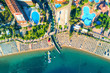 Aerial view of transparent turquoise sea, beautiful sandy beach with colorful chaise-lounges, boats, green trees, pool, hotels, buildings at sunset in Icmeler, Turkey. Summer landscape. Top view.
