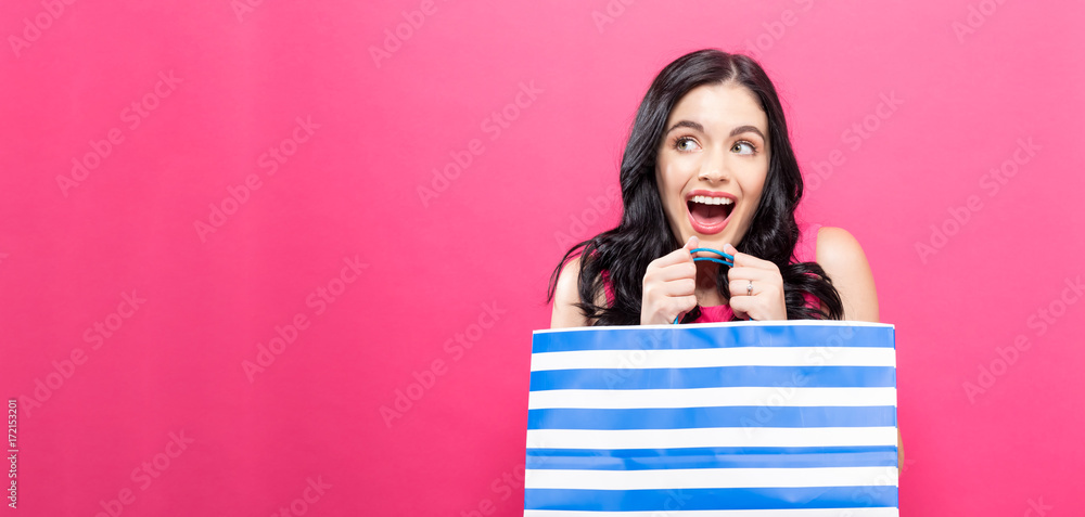 Fototapeta Young woman holding a shopping bag on a pink background