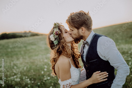 Stampa su Tela Beautiful bride and groom at sunset in green nature.