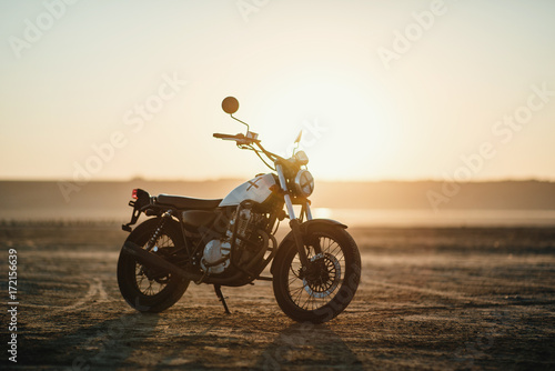 Fotografía old custom beautiful cafe racer motorcycle in the desert at sunset or sunrise