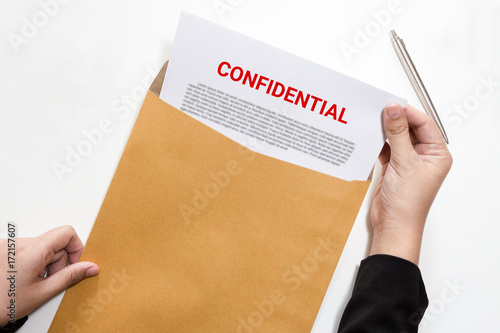 Fotografía  Woman hands holding and looking at confidential document in envelope - business concept
