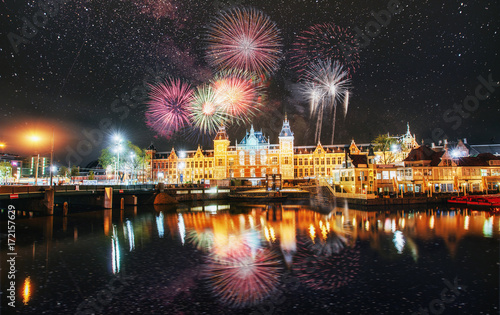 Tuinposter Amsterdam Beautiful calm night view of Amsterdam city. Colorful fireworks on the black sky background. Photo greeting card. Bokeh light effect, soft filter