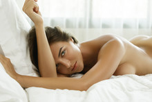 Woman With Sexy And Tanned Body Is Lying On The Bed