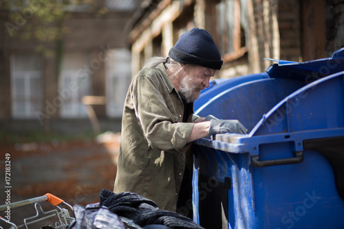Fotografia Beardy homeless man searching for empty bottles in trash can