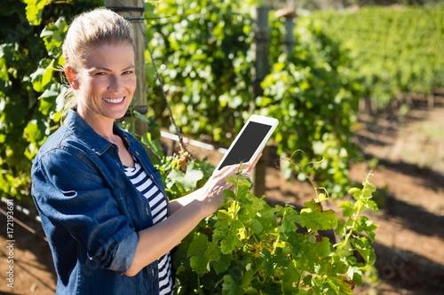 Fotografía  Portrait of female vintner using digital tablet in vineyard
