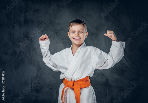 Preschooler boy dressed in a white karate kimono.