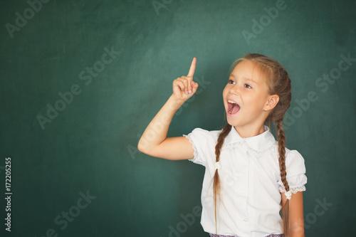 Plakat Uśmiechnięta młoda małe dziecko dziewczyna w szkole na blackboard tle. Koncepcja edukacji i szkoły
