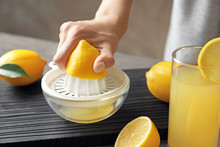 Woman Squeezing Lemon Juice In...
