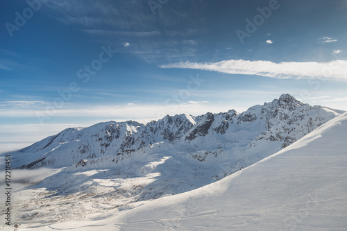 Wide shot aerial view of snow capped cold rock mountains with sunny blue skies