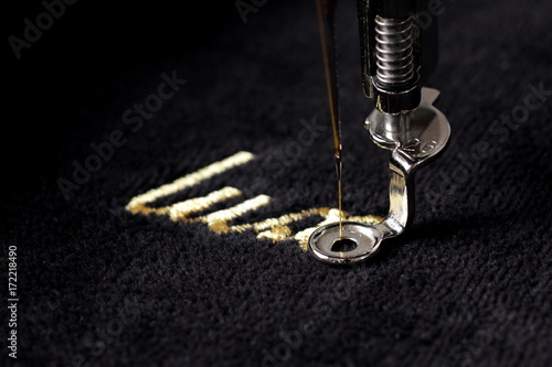 Fotomural embroidery of gold lettering luxury on black velvetely fabric with embroidery
