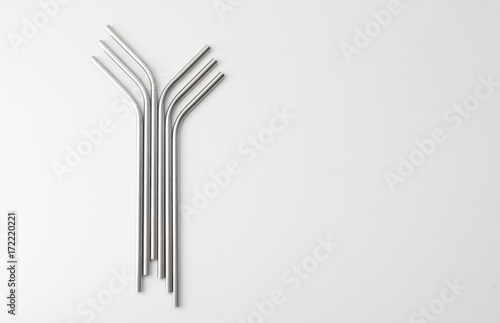High angle view of six metal drinking straws arranged on white background