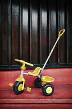 A Child`s Trike On A Red Step