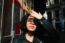 Beautiful Woman Shields Her Eyes From The Sun On Urban Street.