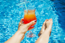 Woman Holds A Cocktail On Swimming Pool Background