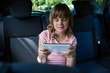 Teenage girl using digital tablet in the back seat of car
