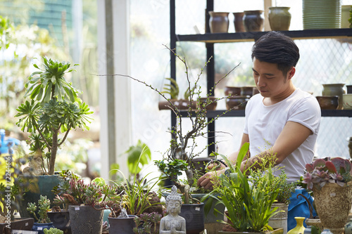 young male florist working in the shop
