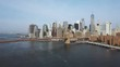 Aerial view of the capital of America, New York. Drone flying up to the Brooklyn bridge through the East river.