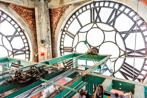 Inside clock tower in old port area with closeup of time wheels levers in city in Quebec region