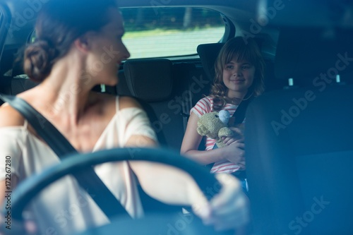 Woman driving a car while daughter sitting in the backseat of Fototapet