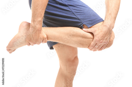 Fototapety, obrazy: Young man suffering from pain in leg on white background