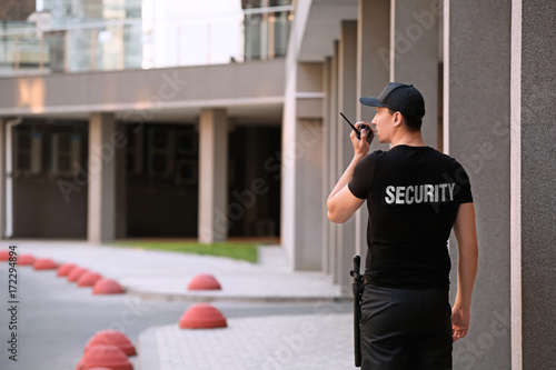 Fotografía Male security guard with portable radio, outdoors