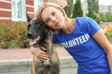 Fototapeta Zwierzęta - Young female volunteer with homeless dog outdoors. Concept of volunteering and animal shelters