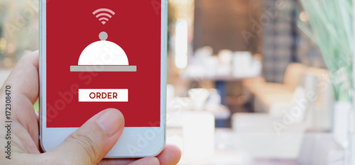 Hand holding smart phone with food online device on screen over blur restaurant background, banner wuth copy space, food online, food delivery concept