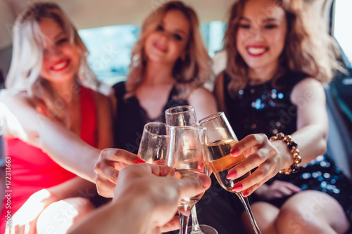 Fotografia Pretty women having party in a limousine car and drinking champagne