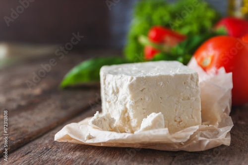 cheese feta-brynza and fresh vegetables, lettuce, tomato, cucumber, pepper on a wooden background in daylight