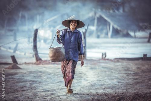 Fotografie, Tablou Woman working on salt field in Thailand, Boiling rock salt, crystallized salt fr