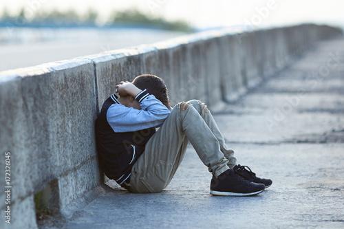 Fototapeta young homeless boy  crying on the bridge