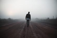 Man Walking On Misty Path