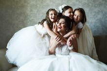 Funny Little Girls In White Dresses Stand Behind Bride Sitting On The Couch