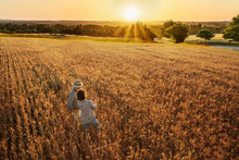 Farmer Couple Standing In Their Wheat Field At Sunset