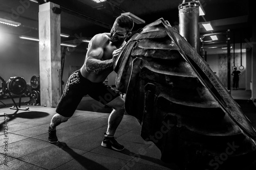 Valokuvatapetti Shirtless man flipping heavy tire at crossfit gym