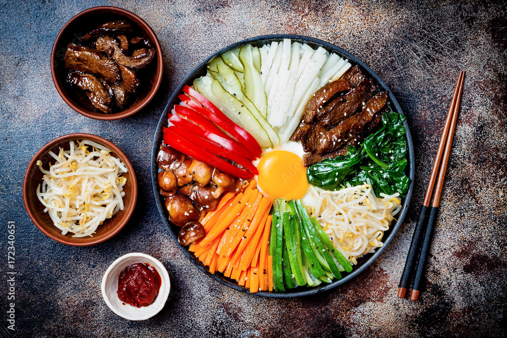 Fototapeta Bibimbap, traditional Korean dish, rice with vegetables and beef. Top view, overhead, flat lay